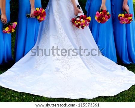 Wedding dress train, summer bridal bouquets, and bridesmaids. - stock photo