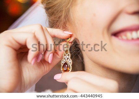 Wedding earrings on a female hand, she takes the earrings, the bride fees, morning bride