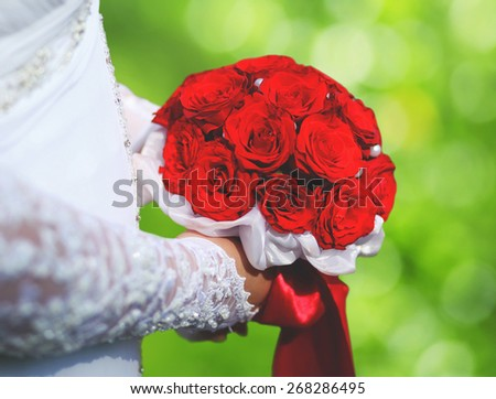 Wedding elegant bouquet of red rose flowers in hands bride on summer background - stock photo