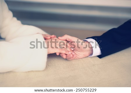 Wedding, engagement and date concept - couple in love, man gently holds the hand of a woman, soft pastel vintage colors - stock photo