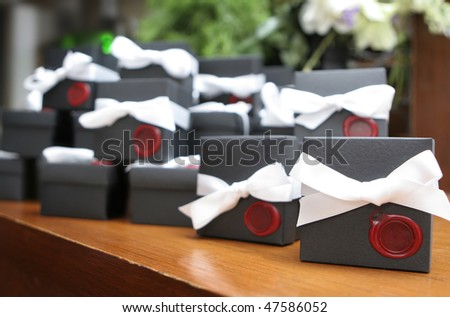 Wedding favors at a reception. Shallow depth of field with only the closest box in focus. - stock photo