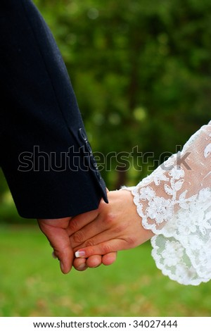 Wedding feelings. Couple holding hands. Natural green background.