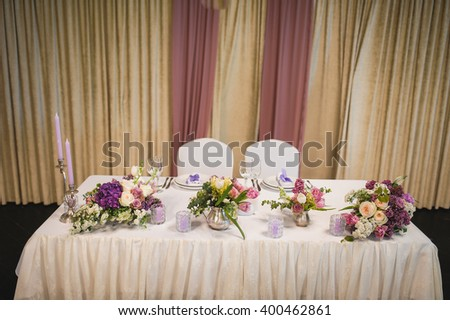 wedding festive table decorated by purple and white flowers with candles on both sides