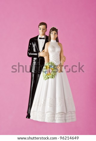 Wedding Figurines towards pink background - stock photo