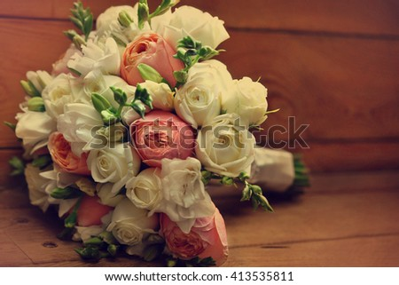 Wedding flower bouquet of roses and freesias on wooden background, selective focus, toned - stock photo