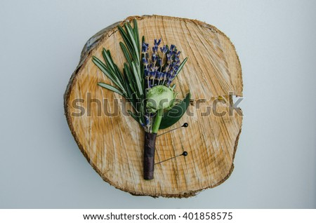 Wedding flower boutonniere with ranunculus, lavender, rosemary on wooden speel. Groom detail, rustic style. Top view, tonal effect. White background. - stock photo