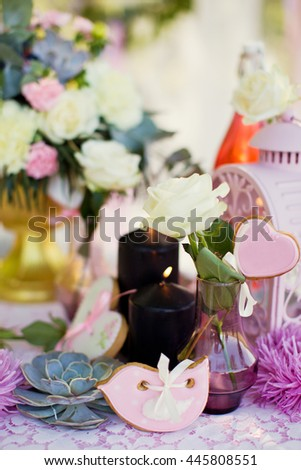 wedding flower composition, candles, cookies and champagne - stock photo