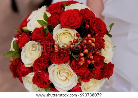 Wedding flowers, a bouquet of red and cream roses with red berries. The bride's bouquet