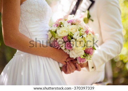 Wedding Flowers Bouquet in Bride Hands with White Dress on Background.