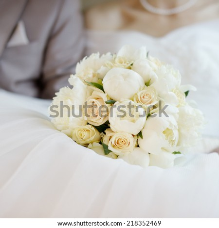 Wedding flowers bouquet on wedding dress - stock photo