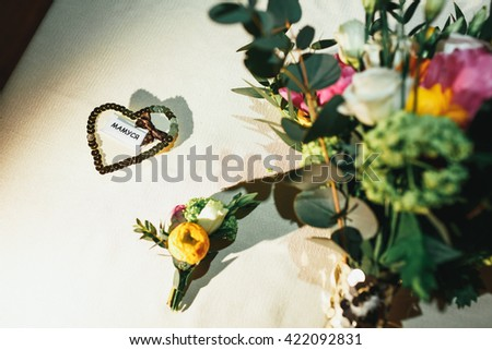 Wedding flowers, boutonnieres and seating cards on the table - stock photo