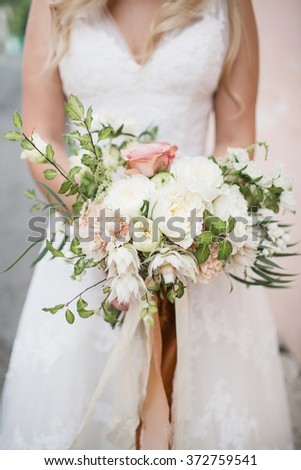Wedding flowers in bride's hands close-up
