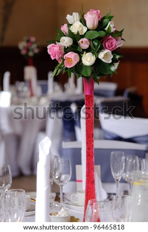 Wedding flowers on red stand at the reception