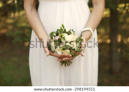 Wedding Flowers Roses Bouquet in Bride Hands with White Dress on Background - stock photo