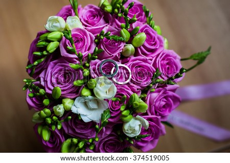 wedding flowers, wedding rings on a white background,wedding bands, wedding rings lie on a wedding bouquet of beautiful pink roses and white flowers,bouquet of roses, wedding preparation - stock photo