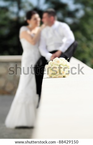 Wedding flowers with bride and groom, focused to wedding bouquet - stock photo