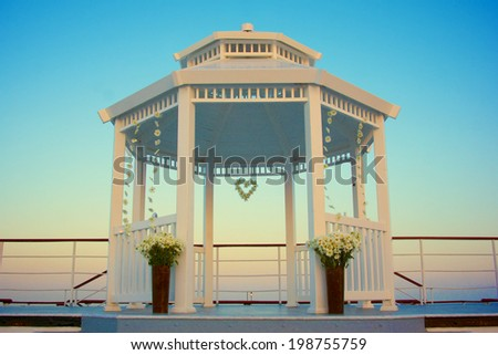 Wedding gazebo decorated with flowers in the light blue of early evening.  - stock photo