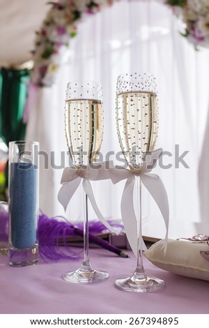 wedding glasses of champagne decorated with strass and ribbon bows - stock photo