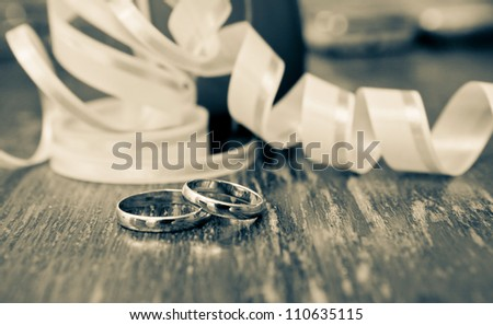 Wedding gold rings of the groom and the bride on a table - stock photo