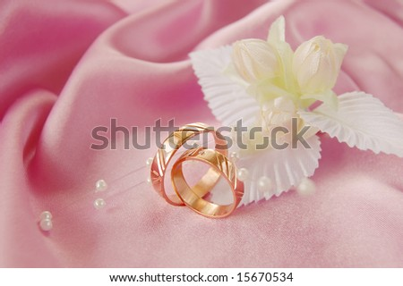 Wedding background pink decoration accessories artificial stock wedding golden rings with decoration on pink satin junglespirit Image collections