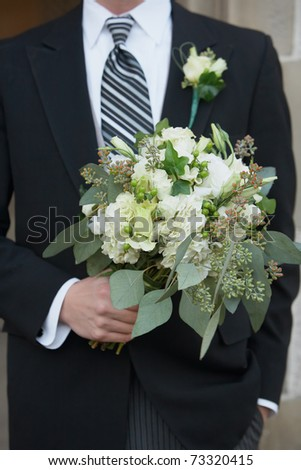 Wedding groom fashion with bride's bouquet of flowers - stock photo