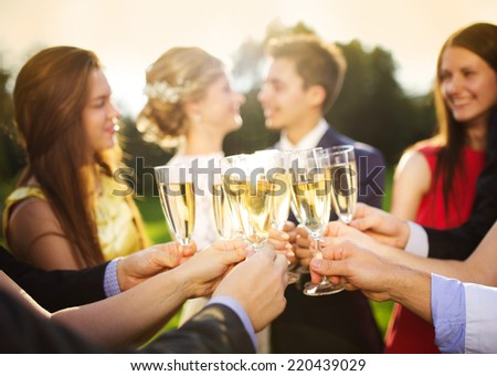 Wedding guests clinking glasses while the newlyweds hugging in the background - stock photo