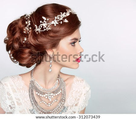 Wedding Hairstyle. Beautiful fashion bride girl model portrait. Luxury jewelry.  Attractive young woman with red hair. - stock photo