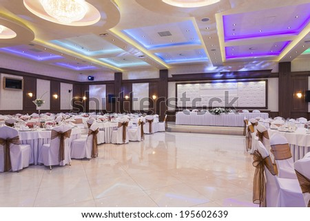 Wedding hall or other function facility with colorful ceiling lights set for fine dining  - stock photo