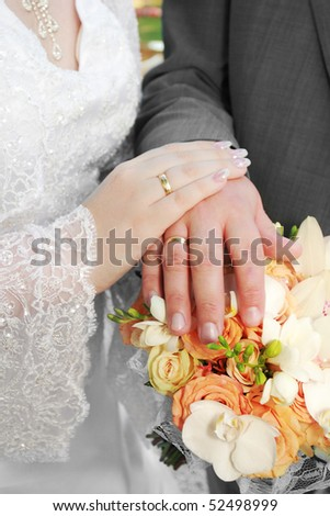 Wedding: hands, rings and bouquet - stock photo