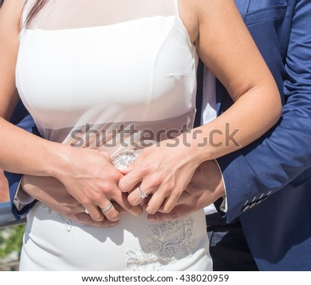 Wedding hands with rings. Groom hugging the bride from behind. Happy newlyweds. Marriage concept. - stock photo
