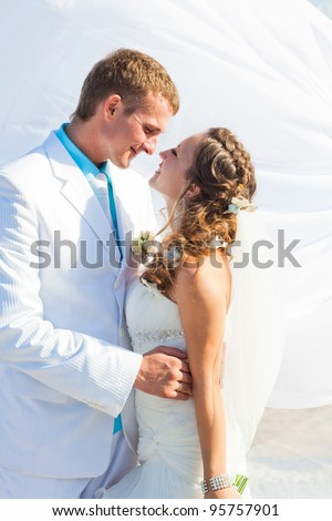 Wedding - Happy kissing bride and groom on white - stock photo