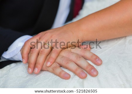 Wedding image with newlyweds holding hands and a gold ring