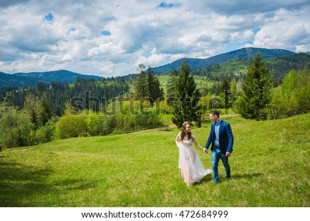 wedding in mountains, a couple in love, mountains background, surrounded dandelions, among the lawn with the green grass, rustic style, girl in long tulle dress, romantic landscape, walking