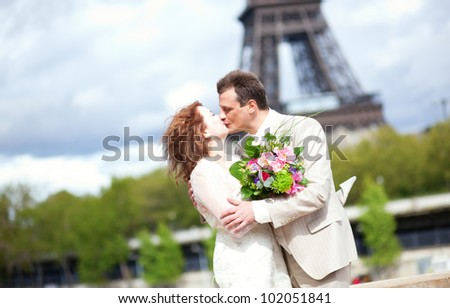 Wedding in Paris. Happy newlywed couple kissing near the Eiffel Tower - stock photo