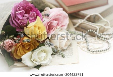 Wedding invitation. Roses with vintage book and pearl necklaces