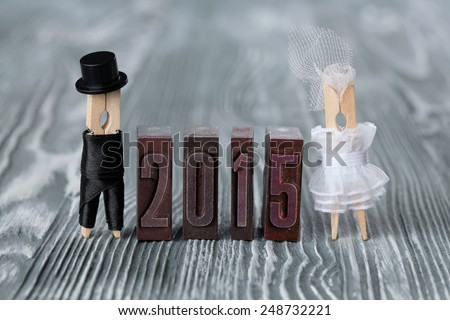 Wedding invitation. 2015 written with colored vintage letterpress. Groom in black suit and bride in white dress. Clothespins. (Soft focus) - stock photo