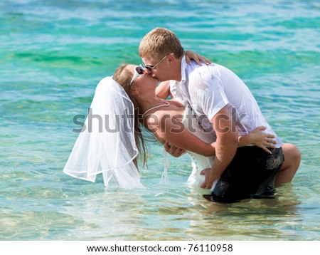 Wedding kiss. Groom holding a bride in his hands - stock photo