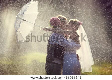 wedding kiss in the rain - stock photo