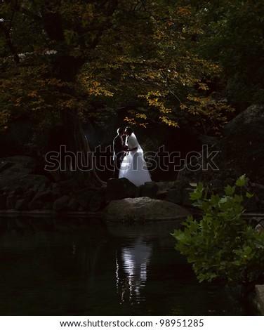 wedding kiss near the lake - stock photo