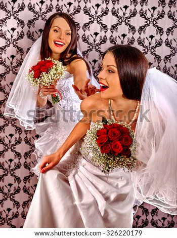 Wedding lesbians girl in bridal dress at home. Wallpaper in background - stock photo