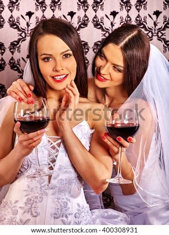 Wedding lesbians girl in bridal dress drinking red wine. Delicate feminine feelings. Wallpaper background. - stock photo