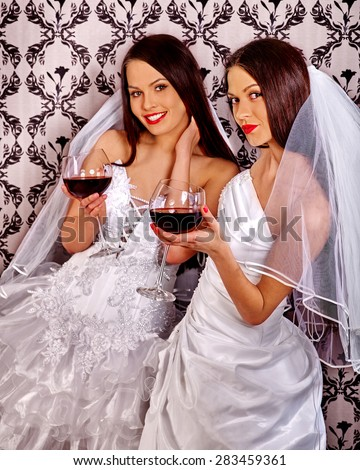 Wedding lesbians girl in bridal dress drinking red wine. Wallpaper background. - stock photo