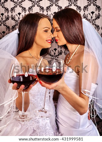 Wedding lesbians girl in bridal dress drinking red wine. Wallpaper background. Lesbians in love. - stock photo