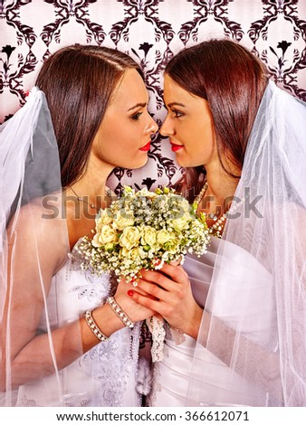 Wedding lesbians girl in bridal dress holding white roses bouquet. - stock photo