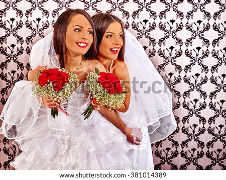 Wedding lesbians girl in bridal dress keeps bouquet. Wallpaper in background