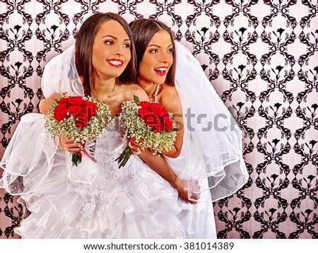 Wedding lesbians girl in bridal dress keeps bouquet. Wallpaper in background - stock photo