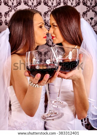 Wedding lesbians girl in bridal dress keeps glass and drinking red wine. Wallpaper background. - stock photo