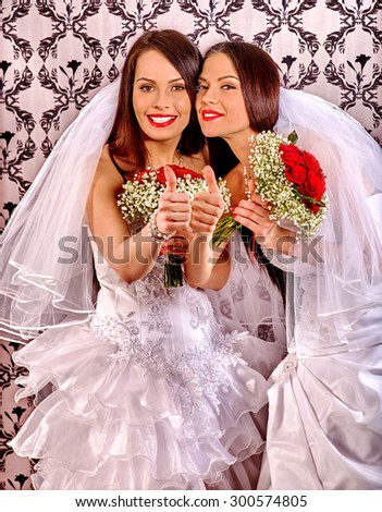 Wedding lesbians girl in bridal dress thumb up. Indoor. - stock photo