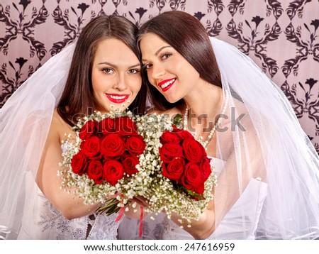 Wedding lesbians girl in bridal dress. Wallpaper in background - stock photo