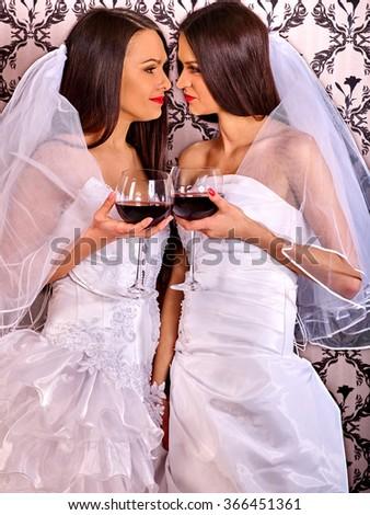 Wedding lesbians girl wearing white long bridal dress drinking red wine. Wallpaper background. - stock photo